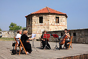 4 women musicians playing chamber music outdoors in ancient fort; entertainment; Baba Vida Fortress; Vidin; Bulgaria, summer