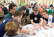 O.U.'s Ben Stuart oversees Matt Junn (center, black shirt) and Isak Hedges (right) work on a battery-powered car during the Russ College of Engineering and Technology research fair/engineering day in the Baker Center ballroom on Thursday, 5/3/07.