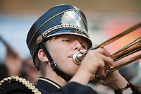Young female band member playing trombone