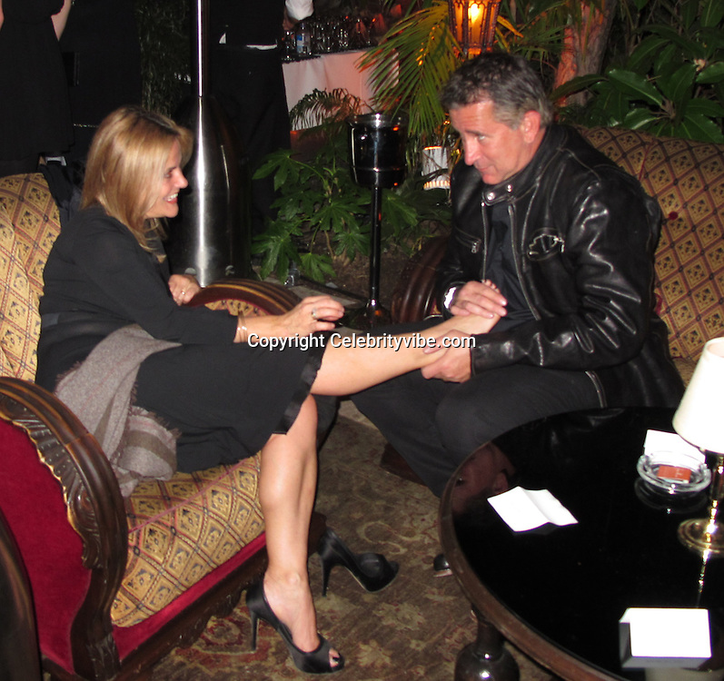 """**EXCLUSIVE**.Anthony LaPaglia and Jennifer..Anthony LaPaglia massages Jennifer's feet..The Weinstein Co. Party for OSCAR Nominated movie """"The King Speech"""".Chateau Marmount Hotel..Hollywood, CA, USA..Monday, January 07, 2011..Photo By CelebrityVibe.com..To license this image please call (212) 410 5354; or .Email: CelebrityVibe@gmail.com ; .website: www.CelebrityVibe.com"""