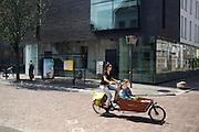 Een vrouw rijdt met een bakfiets met twee kinderen door de Lange Nieuwstraat in Utrecht.<br /> <br /> A woman is cycling on a cargobike with two children.