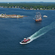 The tug boat Drum Point and the tall ship Oliver Hazard Perry sail past Portsmouth Light House and Fort Constitution at the mouth of  the Piscataqua River off  New Castle, NH during the Parade of Sail event, August, 2016.