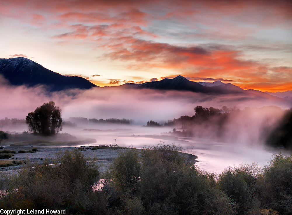 Idaho, east, The red glow of a sunrise reflects colorful light on the fog laden south fork of the Snake River creating ethereal beauty on this autumn morning.