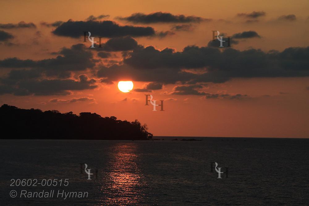 Sun sets over Drake Bay along Pacific Ocean's Osa Peninsula at Corcovado National Park, Costa Rica.