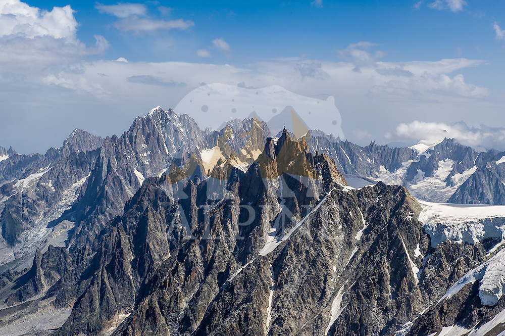 A Summer-season landscape photograph of Aiguille du Midi and Aiguille Verte with their surrounding summits, taken from Aiguille Gouter, Chamonix, France.
