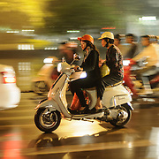 Two women share a scooter on a busy street in Hanoi's Old Quarter.