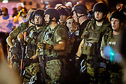 "Police officers from the St. Louis County Police wear cameras as part of their riot gear. Heavily armed police provoked many of the protesters as they swooped in, guns pointing, to  arrest deemed ""troublemakers"" among the protesters in downtown Ferguson following the killing of unarmed Michael Brown (18)."