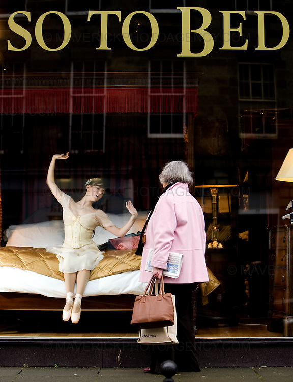 "A shopper looks through a bed shop window as Scottish Ballet dancer Lauren Bryden wakes up, dressed in character as Princess Aurora from the the news Scottish ballet production ""The Sleeping Beauty"""