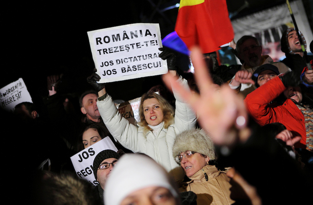 "January 21st 2012, a protester holding a sign that reads ""Romania wake up! Down with the dictatorship! Down with Basescu!"" during a protest against Romania's government at University square in Bucharest, Romania. Hundreds of Romanians rallied  all over the country   to protest against austerity measures, calling for president Basescu and the government to resign."