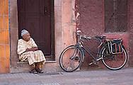 Old man resting at door entrance