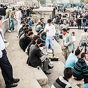 Crowds sit around, some eating their fish sandwich lunches, at the Eminönü waterfront district in the old town of Istanbul