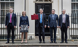 © Licensed to London News Pictures. 22/11/2017. London, UK. Chancellor of the Exchequer Philip Hammond holds his red ministerial box for photographers with his Treasury team (L-R) Andrew Barclay, Economic Secretary, Liz Truss, Chief Secretary, Mel Stride, Financial Secretary and Andrew Jones, Exchequer Secretary outside Number 11 Downing Street on budget day. Photo credit: Peter Macdiarmid/LNP