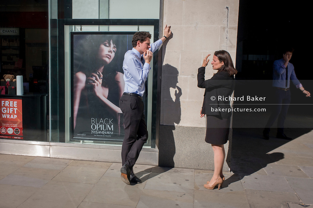 Man and woman chat in the street using hand gestures, a theme echoed in an Yves Saint Laurent fragrance ad.