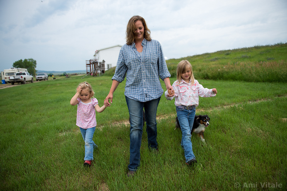 The Nature Conservancy's Matador Ranch Operations Manager Charlie Messerly's wife Jolynn holds her daughter Janae and Layla inEastern Montana  at the Matador ranch &quot;grass bank&quot;. The &ldquo;grass bank&quot; is an innovative way to leverage conservation gains, in which ranchers can graze their cattle at discounted rates on Conservancy land in exchange for improving conservation practices on their own &ldquo;home&rdquo; ranches. In 2002, the <br /> Conservancy began leasing parts of the ranch to neighboring ranchers who were suffering from  severe drought, offering the Matador&rsquo;s grass to neighboring ranches in exchange for their  participation in conservation efforts. The grassbank has helped keep ranchers from plowing up native grassland to farm it; helped remove obstacles to pronghorn antelope migration; improved habitat for the Greater Sage-Grouse and reduced the risk of Sage-Grouse colliding with fences; preserved prairie dog towns and prevented the spread of noxious weeds. (Photo By Ami Vitale)