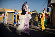 Nayon, Ecuador (outside Quito) during a fiesta through the streets. Clowns dance in the streets with bands and fireworks. Men ride horses through the city. Food is served in the community square.