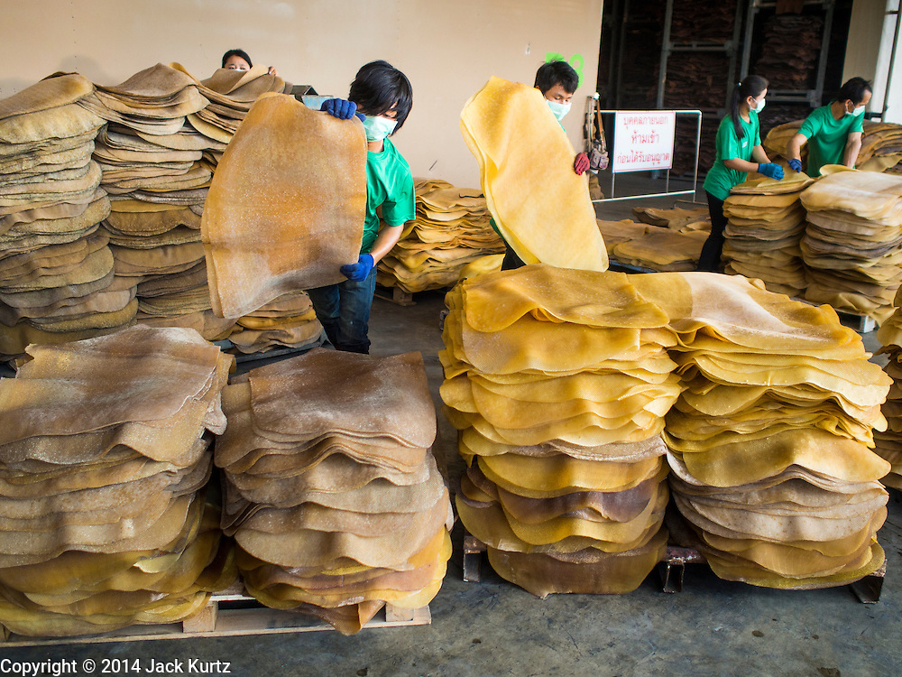 "15 DECEMBER 2014 - KLAENG, RAYONG, THAILAND: TA worker stacks rubber sheets at Supark, a rubber processing plant in Klaeng, Thailand. Thailand is the second leading rubber exporter in the world. In the last two years, the price paid to rubber farmers has plunged from approximately 190 Baht per kilo (about $6.10 US) to 45 Baht per kilo (about $1.20 US). It costs about 65 Baht per kilo to produce rubber ($2.05 US). Prices have plunged 5 percent since September, when rubber was about 52Baht per kilo. Some rubber farmers have taken jobs in the construction trade or in Bangkok to provide for their families during the slump. The Thai government recently announced a ""Rubber Fund"" to assist small farm owners but said prices won't rebound until production is cut and world demand for rubber picks up.      PHOTO BY JACK KURTZ"