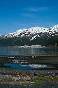 "..The strangest town in Alaska, Whittier - only reachable by tunnel or ship. It's a stop off point for Cruise ships, and the Alaska raildroad. 90% of inhabitants live in one building! Originally established as a military base during World War two.....Reflection in sea water pool, Whittier, Alaska, destination for cruisee ships. The large square building you can see is the Buckner Building,  - ""A city under one roof"". Built in 1953, this derelict building was abandoned but can't be demolished due to the amount of asbestos inside. It was damaged by earthquake in  1964."