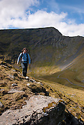 A woman walking at Scales Tarn and Sharp Edge, Blencathra, Lake District, Cumbria, England, UK