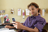 Young man using mobile phone in office