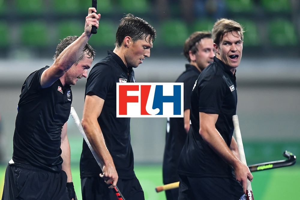 New Zealand's Hugo Inglis (L) celebrates after scoring the first opening goal during the men's quarterfinal field hockey Germany vs New Zealand match of the Rio 2016 Olympics Games at the Olympic Hockey Centre in Rio de Janeiro on August 14, 2016. / AFP / MANAN VATSYAYANA        (Photo credit should read MANAN VATSYAYANA/AFP/Getty Images)