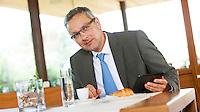 Österreich, Geschäftsmann mit Tablet Computer macht Kaffeepause in Restaurant, Warten auf GeschäftspartnerIn