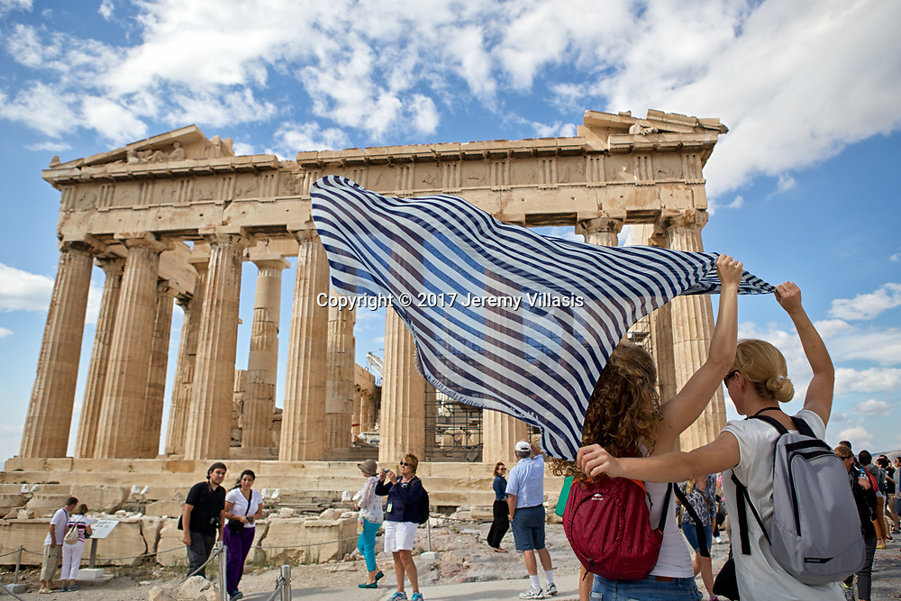 A pair of tourist wave a blue and white scarf, the national colors of Greece in front of the Parthenon.<br /> <br /> The most magnificent temple of the ancient world, the Parthenon, stands on the highest point of the Acropolis. Built between 447 - 338 BC, the temple venerated the cult of Athena Parthenos (Athena the Virgin), the Goddess of Wisdom and Warfare and the Guardian of Athens. <br /> <br /> The temple features 136 fluted Doric columns (in repeated rows of 8 x 17), creating a sense of harmony and order.