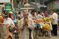 Devout Hindu man prays while walking through the old market in Indra Chawk Square of Kathmandu.