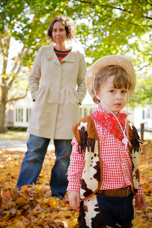 Photo of son in his cowboy costume for halloween with proud mom behind