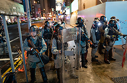 Hong Kong, China. 13th October 2019. Woman suspected of being pro-Beijing is assaulted by pro-democracy protestors in Mongkok district in Kowloon on Sunday evening. This incident was one of several throughout Hong Kong on Sunday which saw acts of vandalism carried out by a minority in the pro-democracy movement.  Riot Police in formation on Nathan Road. Iain Masterton/Alamy Live News.