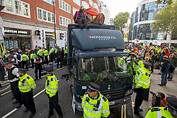 © Licensed to London News Pictures. 08/10/2019. London, UK. An Extinction Rebellion Protester sits on top of a truck outside the Home Office. Photo credit: George Cracknell Wright/LNP