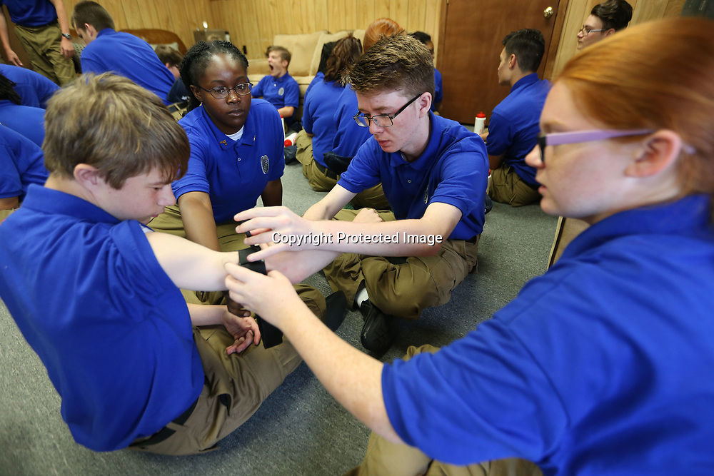 Walker Cary, 15, of Tupelo, holds out his arm as his fellow cadets, Kianna Vance, 15, Jacob Waddley, 16, both of Tupelo, and Lauren Rollins, 14, of Fulton, practice using a tourniquet during first aid training at the Tupelo Poloce Department's Junior Police Academy in Tupelo Thursday morning.