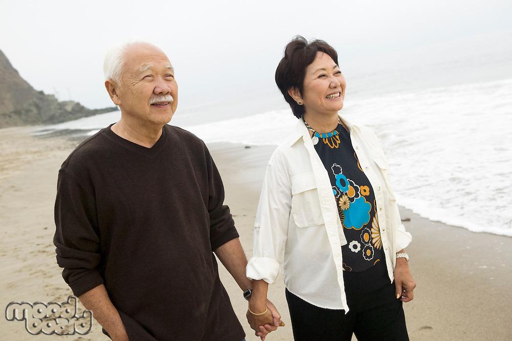 Senior couple on beach holding hands