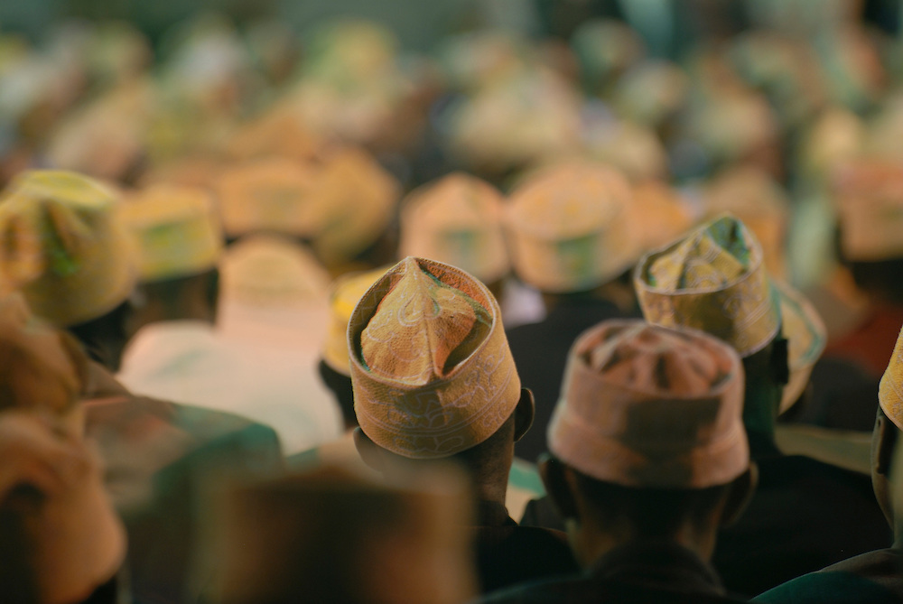 The heads and caps of many men in a mosque at a wedding. Comores. Grand Comore.