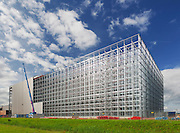 Construction of a vast computerised distribution centre and warehouse. The inside racking system is still visible as the cladding is being installed.