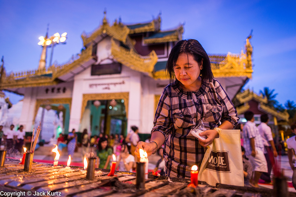 15 JUNE 2013 - YANGON, MYANMAR: A woman makes merit and prays with candles at Shwedagon Pagoda. Shwedagon Pagoda is officially known as Shwedagon Zedi Daw and is also called the Great Dagon Pagoda or the Golden Pagoda. It is a 99 meter (325 ft) tall pagoda and stupa located in Yangon, Burma. The pagoda lies to the west of on Singuttara Hill, and dominates the skyline of the city. It is the most sacred Buddhist pagoda in Myanmar and contains relics of the past four Buddhas enshrined: the staff of Kakusandha, the water filter of Koṇāgamana, a piece of the robe of Kassapa and eight strands of hair from Gautama, the historical Buddha. Burmese believe the pagoda was established as early ca 540BC, but archaeological suggests it was built between the 6th and 10th centuries. The pagoda has been renovated numerous times through the centuries. Millions of Burmese and tens of thousands of tourists visit the pagoda every year, which is the most visited site in Yangon.  PHOTO BY JACK KURTZ