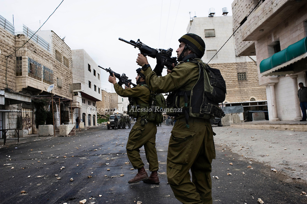 HEBRON : Israeli soldiers take position during clashes with Palestinian stonethrowers in the West Bank town of Hebron on February 25, 2010. Around 100 Palestinians clashed with Israeli troops in Hebron over an Israeli plan to renovate two deeply contested holy sites in the occupied territory..© ALESSIO ROMENZI
