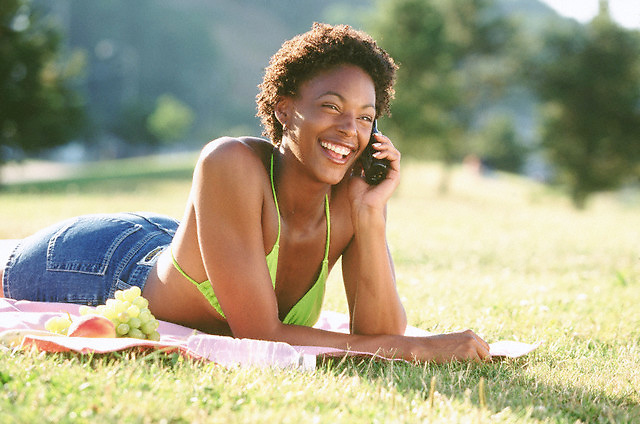 Cheerful woman with a cell phone --- Image by © Jim Cummins/CORBIS