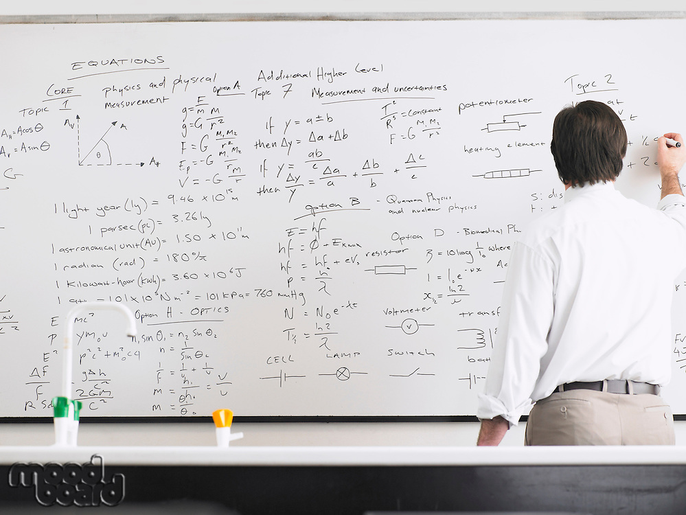 Teacher writing on whiteboard back view