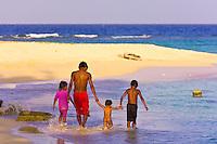 Family walking on the beach on Pelican Island (a.k.a. Icotupo Island), San Blas Islands (Kuna Yala), Caribbean Sea, Panama
