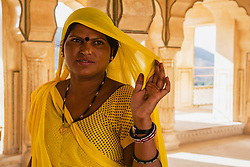 A woman in a colorful sari at the Amber Fort of Jaipur at sunrise, Rajasthan, India,