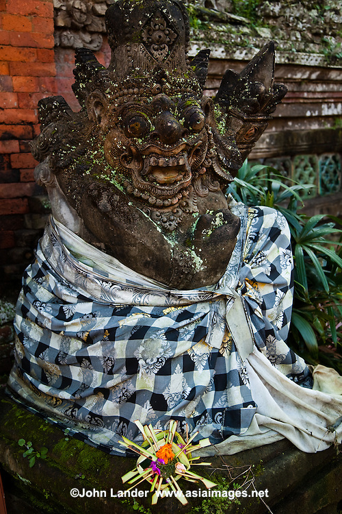A Balinese togog is a decorative sculpted head, often decorated with flowers.  The faces and expressions taking form from Balinese folk tales and legends.  This one is wearing a Poleng.