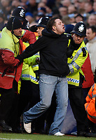 Photo: Daniel Hambury.<br />Arsenal v Cardiff City. The FA Cup. 07/01/2006.<br />A Cardiff fan runs onto the pitch and is tackled by stewards and police.