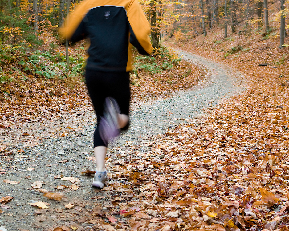 Female runner on a country road during autumn in Vermont.