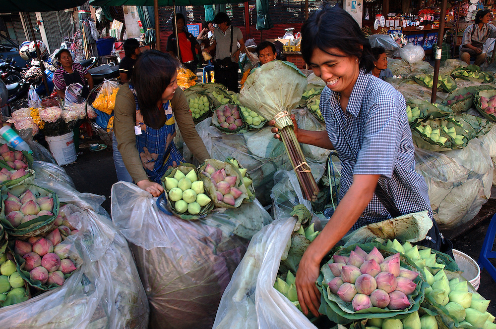 Vendor prepares lotus flowers for sale at Pak Klong Talat Market, Bangkok, Thailand