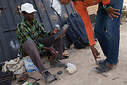 Migrant worker from Niger works as cobbler.