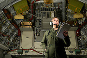A U.S. Air Force loadmaster runs down her checklist in the cargo area during preflight...Air Force aircraft transport most of the supplies and military equipment to the combat zone. Specialists must weigh, sort and load all of the gear before it heads to its location abroad. Air Force loadmasters and pilots ensure the safe transport of all equipment required in the field.