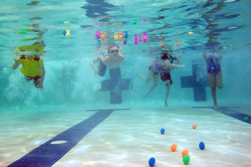 A group of kids dive into the water to gather as many Easter eggs as possible during the Under the Sea Adventure at the Don Rodenbaugh Natatorium in Allen on Saturday, March 30, 2013. (Cooper Neill/The Dallas Morning News)