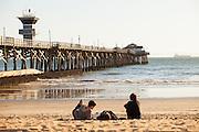 Friends Sitting On The Beach At Seal Beach Pier