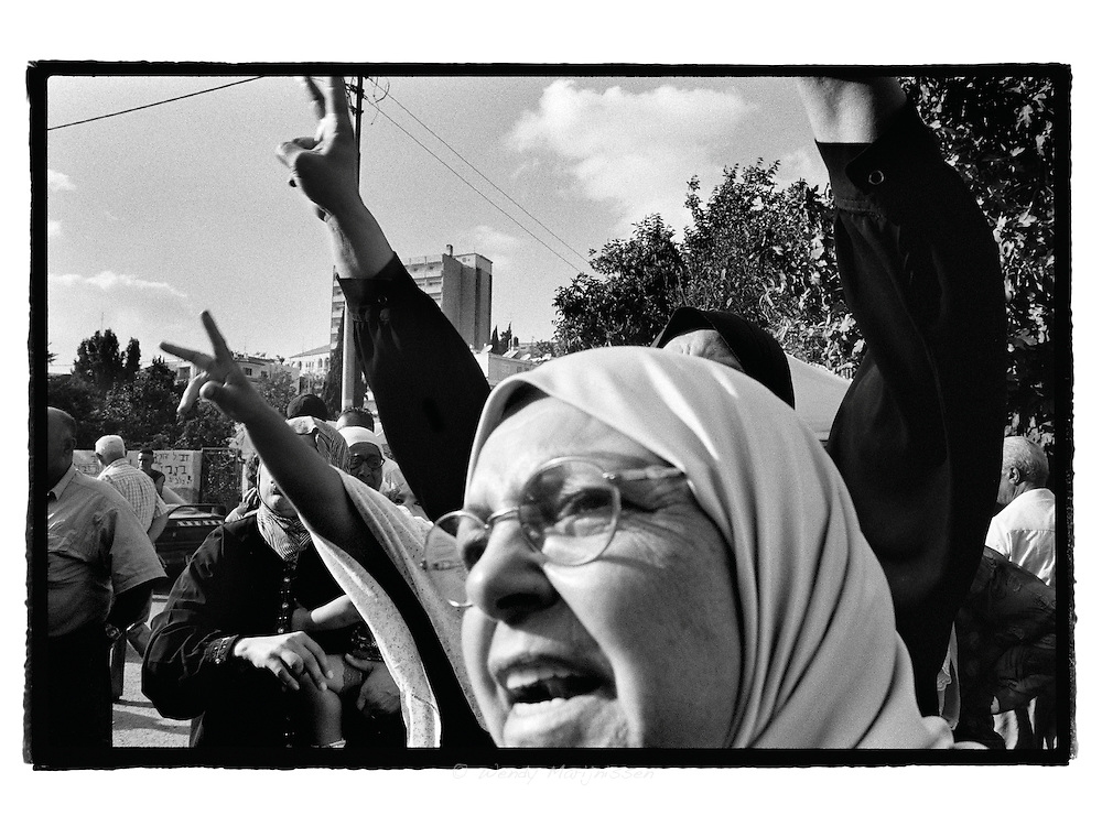 Neighbours and members of the al-Ghawi family scream slogans and hold up v signs for peace, during a protest in front of their former house, while two Israeli parliamentarians are touring her home and showing support to the settlers  occupying it.