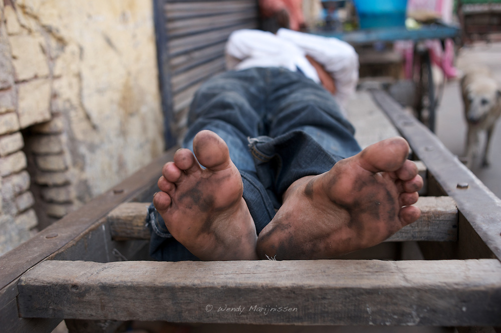 Feet of a peddle rickshaw driver that is sleeping and resting in between work. Old Delhi, New Delhi, India